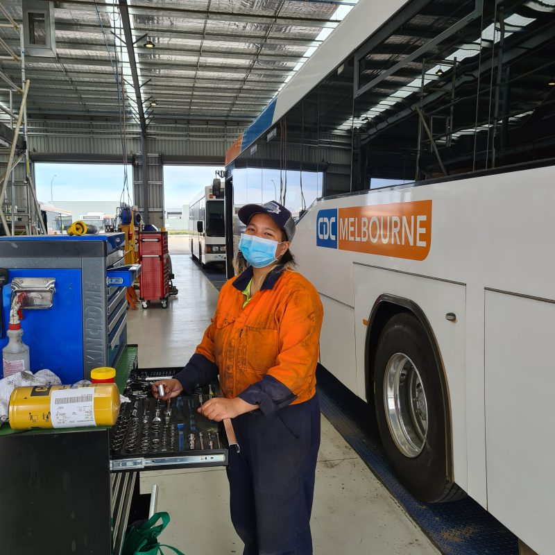 Female assistant mechanic apprentice smiling and doing her job in front of a CDC VIC bus