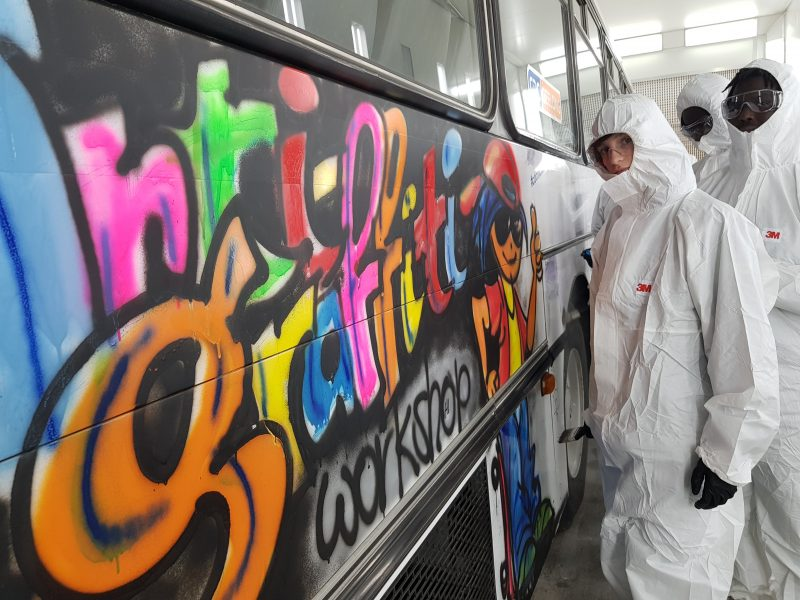 Youth Stand In Front Of A Bus With Graffti